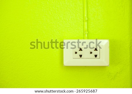 on a green wall, there is a socket with two outlets - stock photo