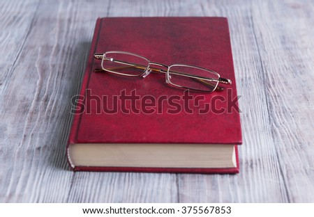 On a light background is a wooden red book in hard cover and glasses for poor vision to read - stock photo