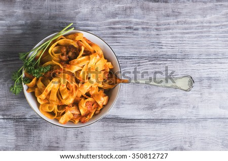 On a light wooden background in vintage style food dinner plate with Bolognese Tagliatelle pasta, fork, green curly parsley, top view - stock photo