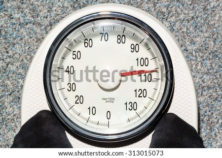 on a personal scale is a fat person. symbolic photo for overweight and fettlleibigkeit. - stock photo