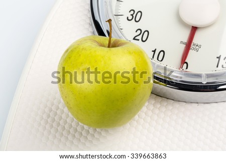 on a personal scale is an apple. photo icon for weight loss and healthy, vitamin-rich diet. - stock photo