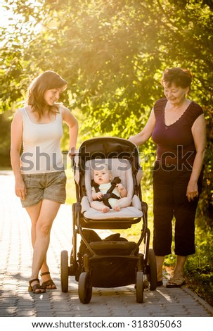 On a walk - grandmother with her daughter and her granddaughter in stroller - stock photo