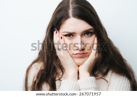 on a white background young girl with long hair sad - stock photo