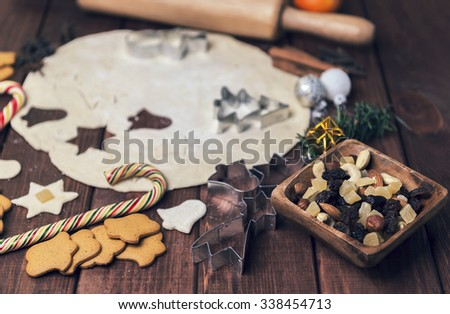 On a wooden desk background Christmas composition - candy cane, dough figurines, Christmas balls, raisins, nuts, cinnamon sticks, cookies, anise, mandarins; bump; roll out the dough layer; plunger - stock photo