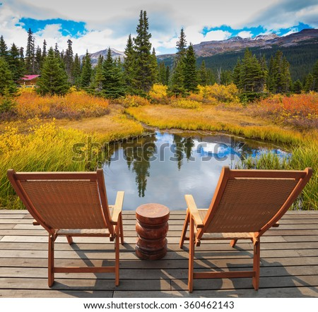 On a wooden scaffold there are two convenient wattled chaise lounges beside  lake. Cold autumn day in the Rocky Mountains of Canada - stock photo