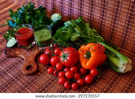 On a wooden table are fresh vegetables from the garden of which the housewife has prepared two different cocktail, one tomato and one cucumber - stock photo