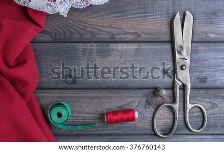 On a wooden table red and maroon cloth tape for removal of measures, tailor scissors, a metal thimble spool of thread with a needle, top view, empty place for your text - stock photo