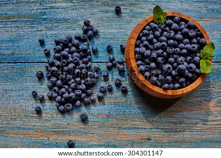 On a wooden table, there is a small wooden plate in which blueberries sprinkled with slide - stock photo