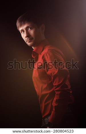 On dark background young man poses for photograph - stock photo