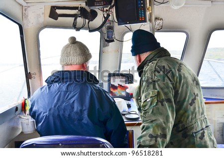 On fishing boat - studying a sonar screen - stock photo