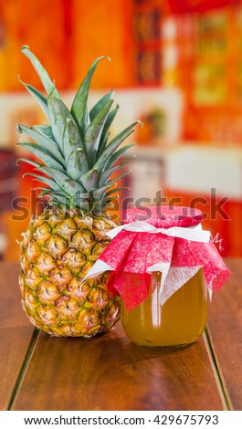 On one side a pineapple on the other a delicious jam made of these fruit on a wooden table, - stock photo