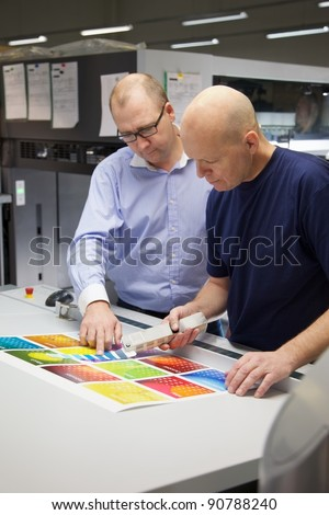 On Press in a Printing Factory. Two men checking the color of a colorful printed calendar sheet with a swatch. - stock photo