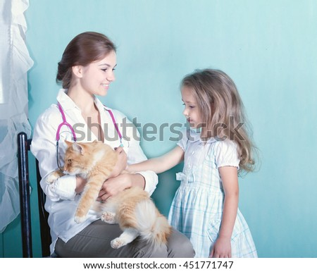 on reception at the vet.little girl stroking her cat who sits in the hands of a girl vet.toned  - stock photo