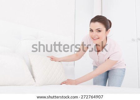 On right place. Pretty young female is putting white pillow on purely white bed next to another one on white background of bedroom - stock photo