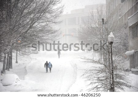 On snow-covered street. People go along the street during a snowfall. - stock photo