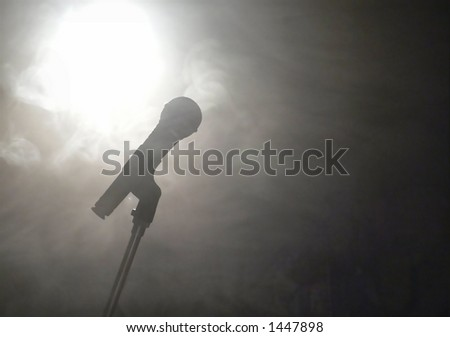 On stage scene of wireless microphone silhouetted against smoky spotlight. The microphone is slightly left of center and the spotlight is upper left.  Copy space to the right. Horizontal orientation.  - stock photo