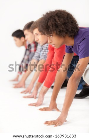 On starting line. Group of young multi-ethnic men standing on starting line and looking forward while isolated on white - stock photo