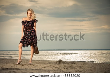 On the beach. A young pretty lady standing against the background of a seashore. - stock photo