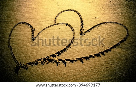 On the beach, the sand is drawn sketch - two hearts. - stock photo