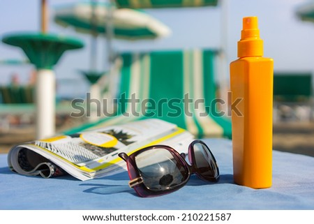 on the beach under the umbrella ready for the sun - stock photo