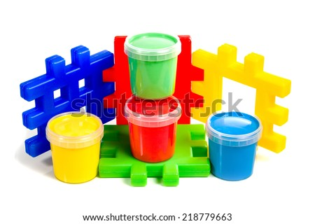 On the bright a colorful children's constructor are four jars of paint isolated on white background - stock photo