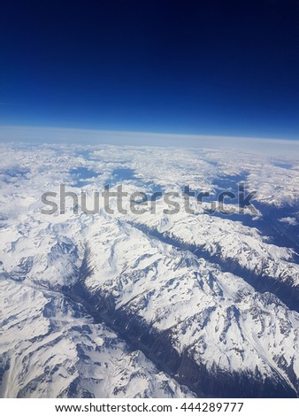 on the edge of the atmosphere with horizon over alpine mountains in europe with blue sky - stock photo