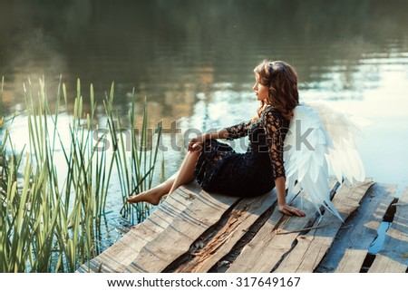 On the pier near the river sits a girl angel. Her black dress and white wings. See more photos of this series. - stock photo