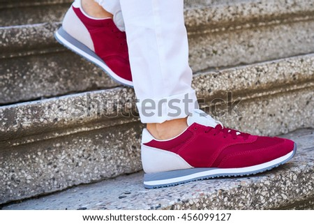 On the stairs a girl in white pants and red sports shoes, fashion street style, space for text - stock photo