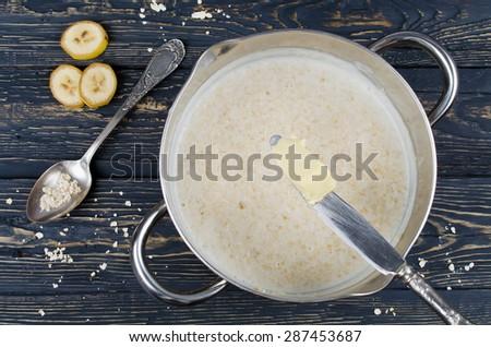 On the table a pot of porridge ready. Oatmeal and banana - stock photo