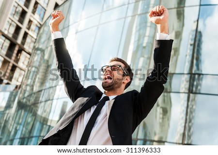 On the top of business world. Low angle view of excited young businessman keeping arms raised and expressing positivity while standing outdoors with office building in the background - stock photo