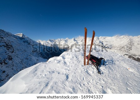 On the top of the mountain, pair of back country - tour ski and a backpack with avalanche safety tools. Scenic high mountain background (Gran Paradiso peak, 4061 m). - stock photo