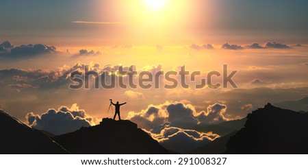 On the top of the world. A man standing on the top of the mountain above the clouds.  - stock photo