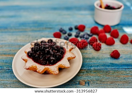 On the vintage wooden table is a plate of fresh pastry  star-shaped, filled with fresh blueberries and black currants - stock photo