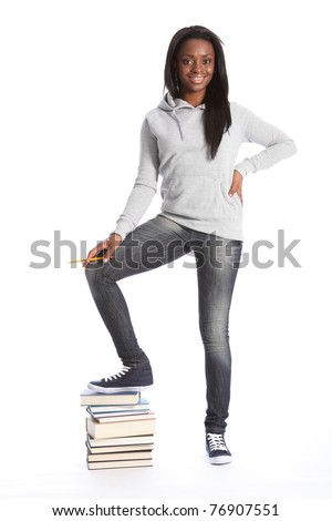 On top of school work. Smiling and relaxed standing pose from beautiful young black teenage student girl, wearing grey hoodie sweater and blue jeans. Girl has one foot on top of a pile of books. - stock photo