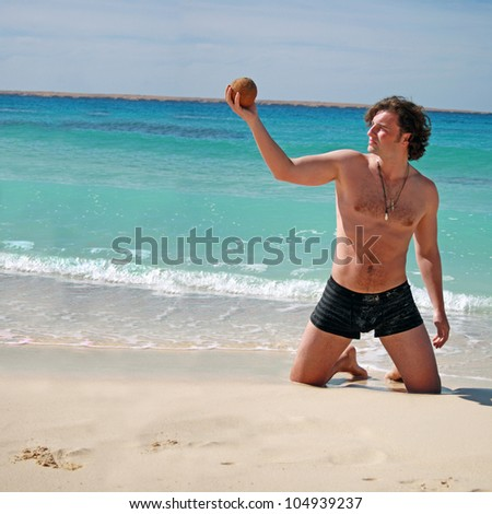 on vacation at the beach posing with coconut - stock photo