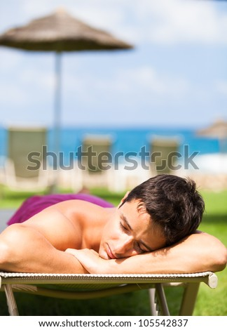 On vacation: young man sunbathing and relaxing on a deckchair near the beach - stock photo