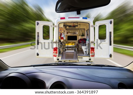 On windshield ,blur image of ambulance on the road as a background. - stock photo