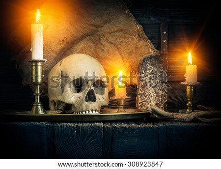 On wooden background skull and candles - stock photo