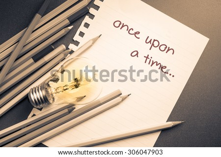 Once upon a time on paper with pencils and lightbulb - stock photo