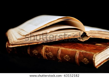 Once upon a time: Two ancient books (one opened) shot on black background. The books are in bad condition. - stock photo
