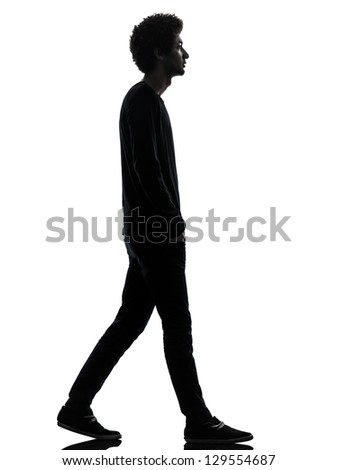 one african handsome young man walking  in silhouette studio isolated on white background - stock photo