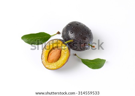 one and half washed plums on white background - stock photo