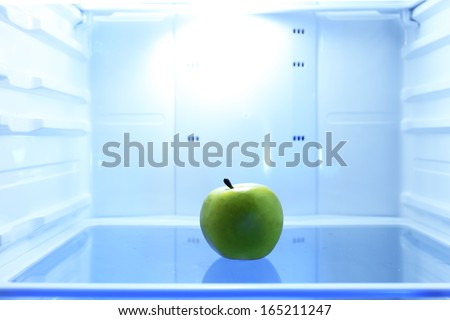 One apple in open empty refrigerator. Weight loss diet concept. - stock photo