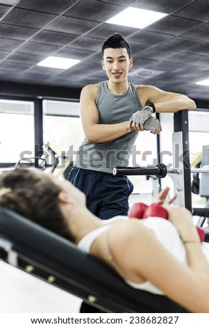 One asian man flirting with a cute girl in a Health Club during a break. - stock photo