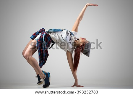 One attractive happy fit cute hipster young woman wearing casual clothing and beanie dancing. Modern style beautiful dancer girl working out, doing backbend, bridge exercise. Studio, gray background - stock photo