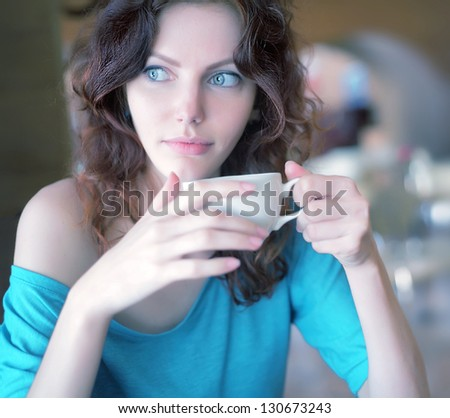 one attractive redhead woman drinking coffee against a bokeh background - stock photo