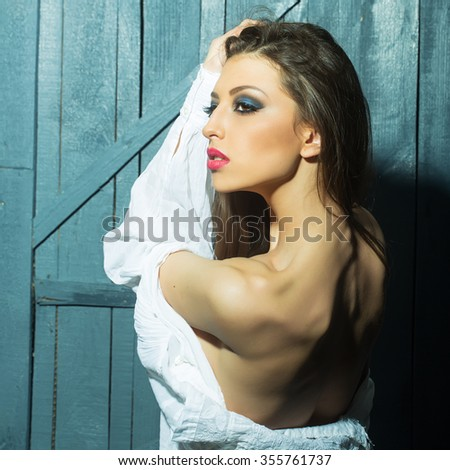 One attractive sensual fashionable young brunette pensive woman with bright makeup and beautiful body in white blouse standing with raised hand in studio on wooden wall background, square picture - stock photo