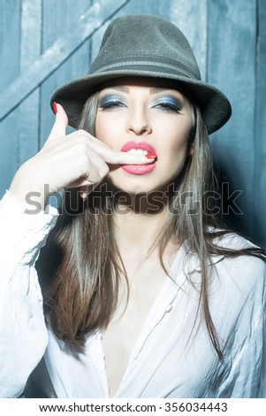 One attractive sensual fashionable young brunette pensive woman with bright makeup and beautiful hair in white blouse and hat with finger in mouth in studio on wooden wall background, vertical picture - stock photo