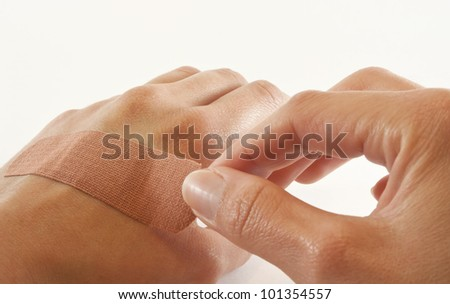 One bare female hand sticking bandaid over cut on the other hand. - stock photo