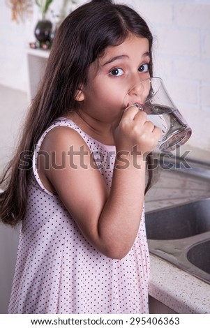 One beautiful middle eastern little girl with pink dress and long dark brown hair and eyes on white kitchen,helping parents to wash dishes and drinking water and smiling looking at camera studio shot. - stock photo